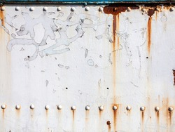 White peeling paint rust texture grunge background of a white painted vintage cast iron textured panel frame with metal rivets, stock photo image