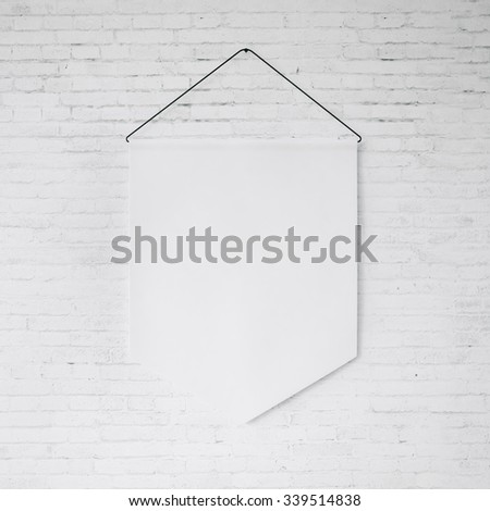 White pennant hanging on the white bricks wall at background. 3d render