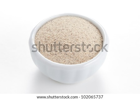 White Pepperground in a white bowl on white background. Used as a spice in cuisines all over the world.