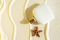 white perfume bottle on a sandy textured background with seafish. Summer scent concept for vacation