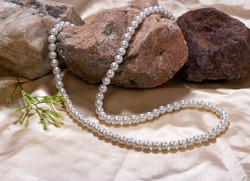White perls neckless with marble stone on pink silk cloth