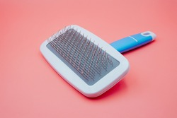 white pet glooming comb and brush for dog and cat hair in blue handle for pet salon isolated on pink background