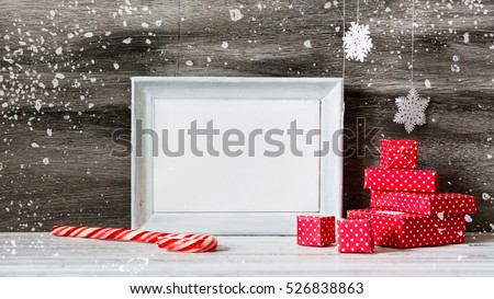 White photo frame with christmas decoration on the wooden table. Red boxes and snowflakes on the grey background. New year greeting card template. Holiday mock up. Scandinavian style.   #526838863