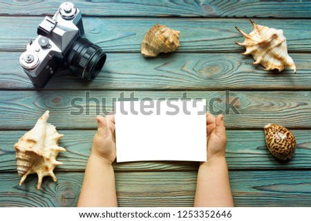 white photo paper in the hands of a child, seashells, retro camera on a wooden background. tourism, travel, vacation at the resort.