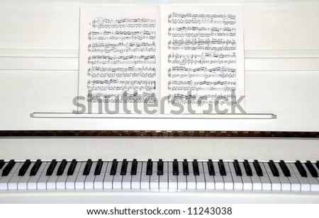 White piano with sheet music