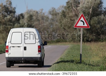 White pick-up going on a contryside road with a sharp corner sign on a lovely day - stock photo