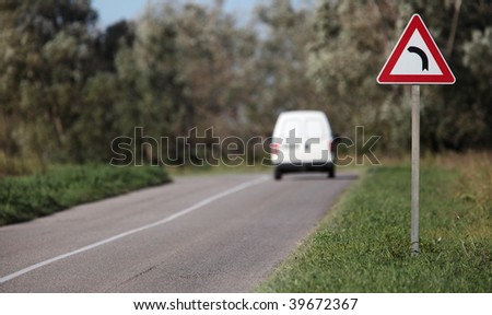 White pick-up going on a contryside road with a sharp corner sign on a lovely day