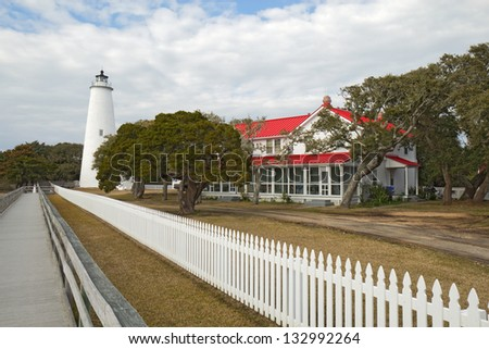 White picket fence and walkway lead past the red-roofed keepers quarters towards the tower of the Ocracoke Island lighthouse on the outer banks of North Carolina