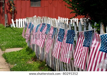 White picket fence decorated with the American flag.