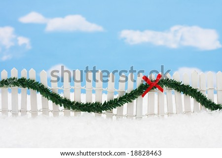White picket fence with green garland and red bow, merry Christmas
