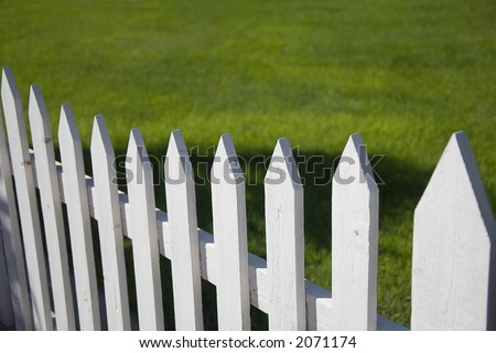 White picket fence with green grass background