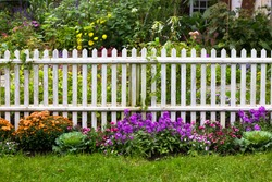 White picket fence with pretty flowers in a yard