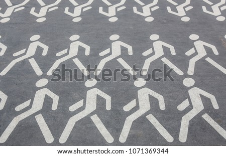 white pictograms of people walking in rows on the asphalt #1071369344