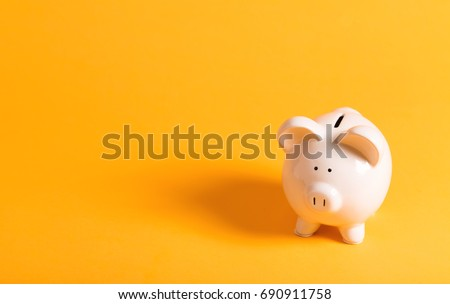 White piggy bank on yellow #690911758
