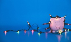 White piggy bank with Christmas string lights on happy December festival, Enjoy savings for spending money on the holiday's concept.