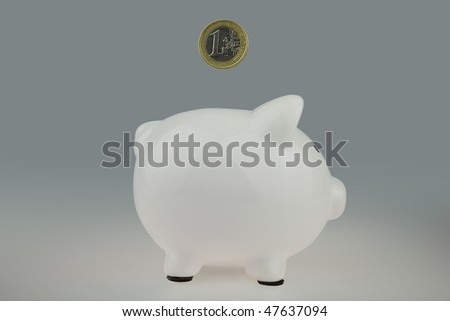 White Piggy bank With One Euro Coin falling from above and heading for the money slot,