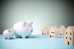 White piggy banks looking at little houses wooden model on the blue background and green background behind with copy space. Concept loan, saving money, investment, save money in the future.