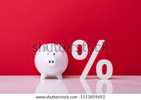 White Piggybank And Percentage Symbol Against Red Wall