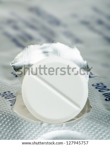 White pill in a pack very close up. Macro studio shot