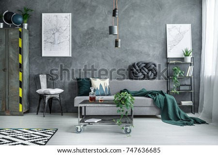 White pillow on black chair between metal wardrobe and grey sofa in dark industrial living room with city map on the wall