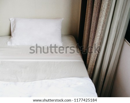 White Pillow on white bed near the Curtain with window in comfortable bedroom design. #1177425184