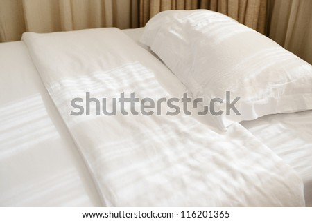 White pillows and bed in bedroom.