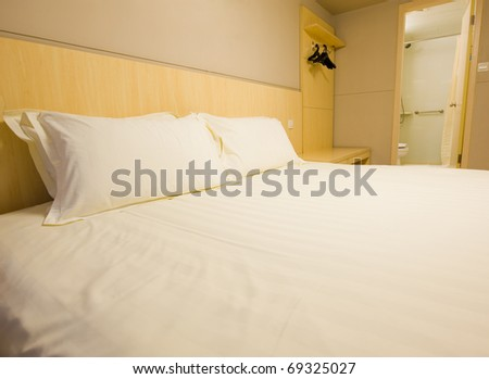 White pillows and bed in white bedroom