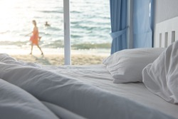 White pillows and bedding sheet in clean hotel bedroom with woman walking on the beach, sea view background, happy summer holiday at luxury resort