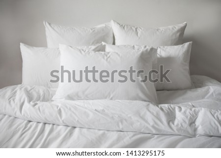 White pillows, duvet and duvet case in a bed. White bed linen on a white bed. Bedroom with bed and linen.