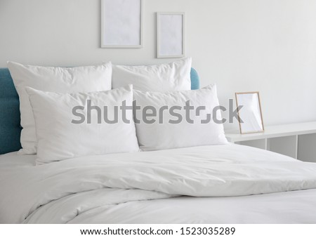 White pillows, duvet and duvet case on a blue bed. White bed linen on a blue sofa. Bedroom with bed and bedding and poster frame mock up on the wall. Left side view.