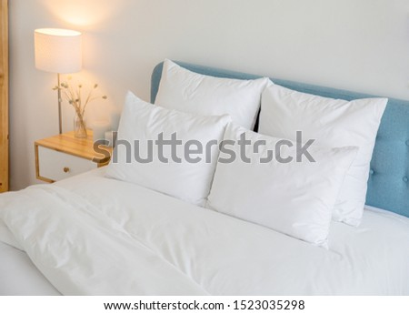 White pillows, duvet and duvet case on a blue bed. White bed linen on a blue sofa. Bedroom with bed and bedding. Right side view.