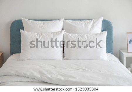 White pillows, duvet and duvet case on a blue bed. White bed linen on a blue sofa. Bedroom with bed and bedding. Front view.