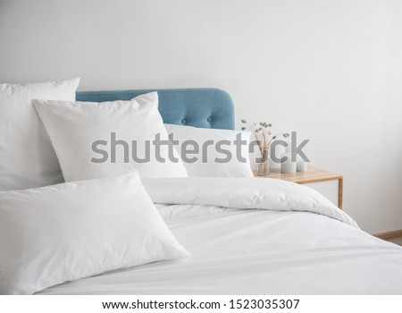 White pillows, duvet and duvet case on a blue bed. White bed linen on a blue sofa. Bedroom with bed and bedding. Messy bed. Left side view.