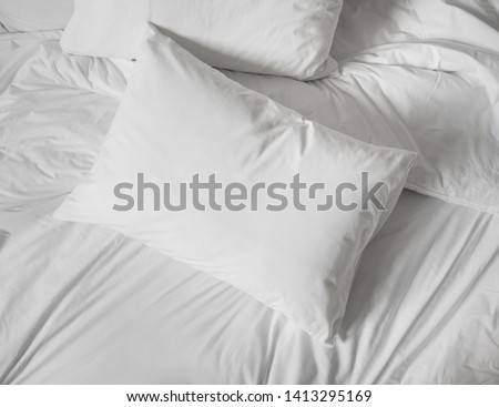 White pillows, duvet and duvetcase in a bed. Messy bed with white bed linen.