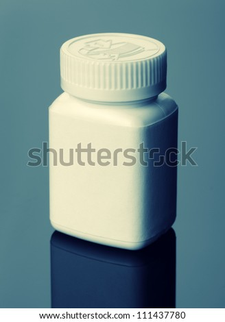 White pills bottle. Toned in blue - stock photo