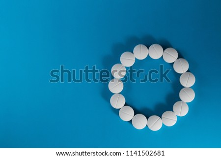 White pills in the form of a circle on a blue background, copy space.