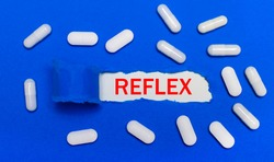 White pills lie on a beautiful blue background. In the center is white paper with the inscription REFLEX. Medical concept. View from above.