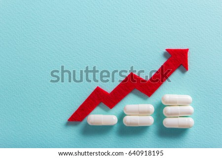 White pills on a green background. Increase the dosage of the medicine. Growing diagram up with a red arrow. Empty place for text copy paste Stockfoto ©