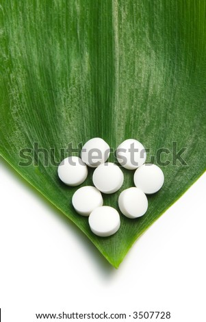 white pills on a green leaf, natural medicine concept