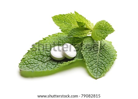 White pills on a green leaves of mint (Melissa officinalis) isolated on white background