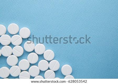White pills on blue background