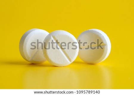 White pills on yellow background