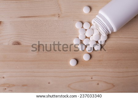 White pills spilled from a pill bottle on wooden table.