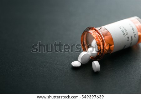 White pills spilling out of a toppled bright red orange pill bottle