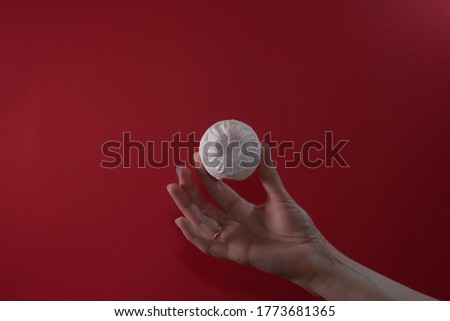 white-pink marshmallows in a female hand on a red background