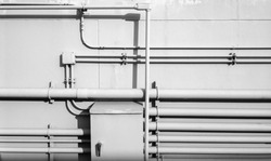 White pipe on wall background, pipe for water system and electricity system on white concrete wall of building texture background, horizontal line, black and white, monochrome tone