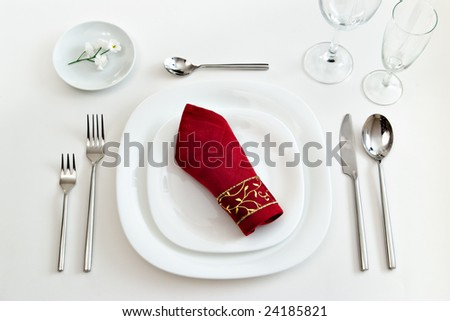 white place setting with dark red napkin