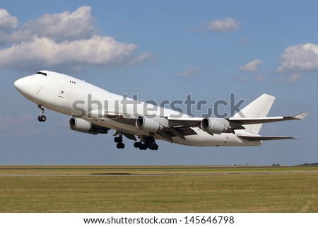 White plane taking off with clouds in the blue sky
