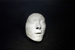 white plaster cast of a person on black background, symbol for isolation, human psyche