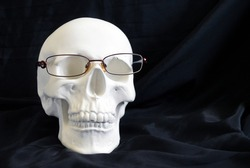 White plaster sculpture in the shape of a skull on a black fabric background